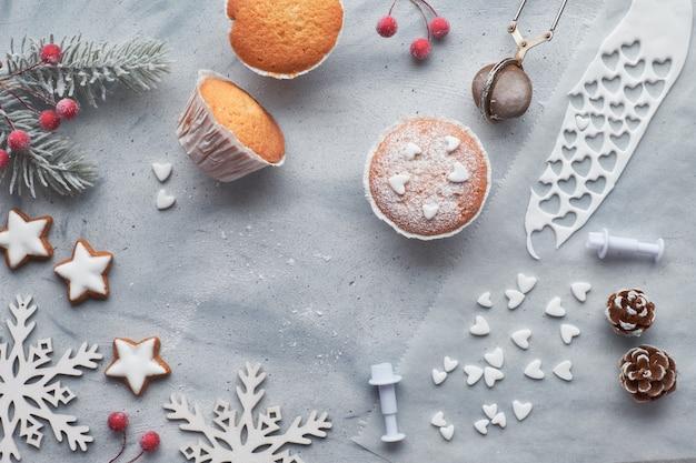 Вид сверху на стол с посыпанными сахаром маффинами, помадной глазурью и печеньем