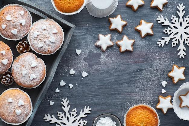 Вид сверху на стол с посыпанными сахаром маффинами, помадной глазурью и печеньем из рождественских звезд на темном дереве