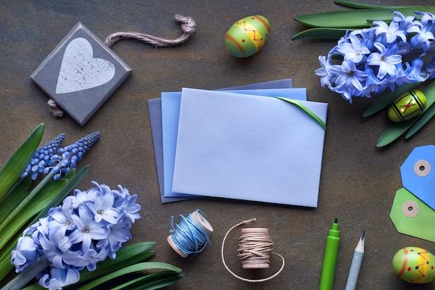 Вид сверху бумажных карт с копией пространства, синие цветы гиацинта и пасхальные яйца на темном столе