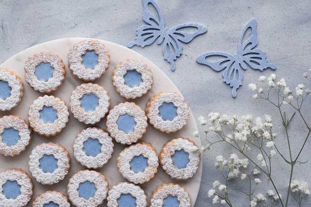 花と蝶で飾られた青い窓ガラスの花リンザークッキーのトップビュー