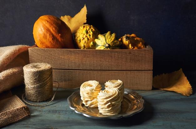 暗い素朴な木のカボチャと秋の装飾で作られた自家製マシュマロ