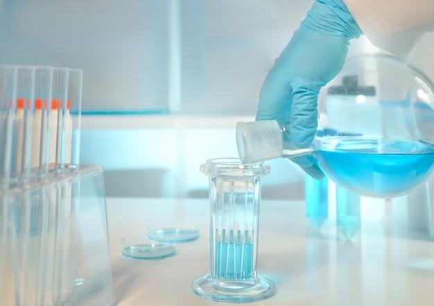焦点が合っていない生物学的または生化学的研究室、手袋をはめた手でフラスコをクローズアップ