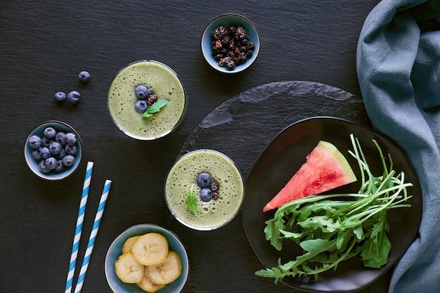 暗いスレートテーブルの上のガラス瓶に緑のルッコラ、バナナ、スイカのスムージー、
