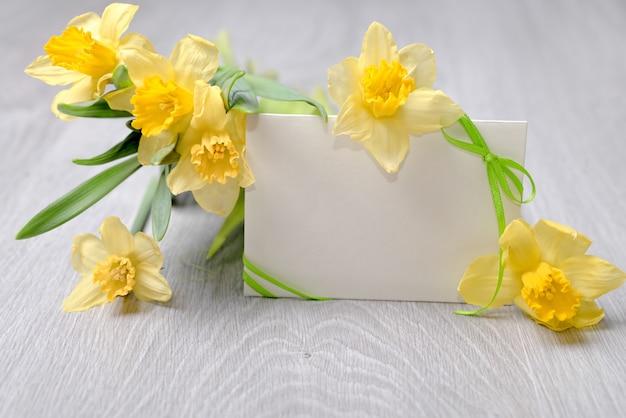 リボンと水仙の花を持つ空白の紙カード