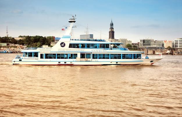 観光客とボートはハンブルクのエルベ川に行く
