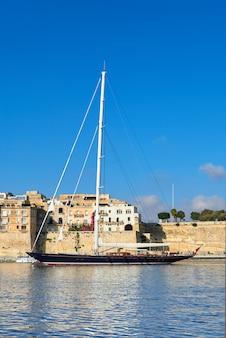 明るい日に帆船がグランドバレッタ湾に入ります