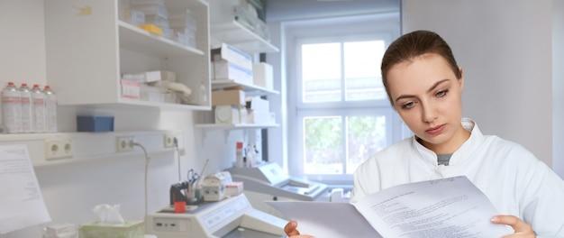 科学研究室、パノラマ画像で印刷されたメモを読む若い女性科学者