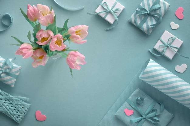 Синий фон с розовыми тюльпанами, полосатой оберточной бумагой и подарочными коробками