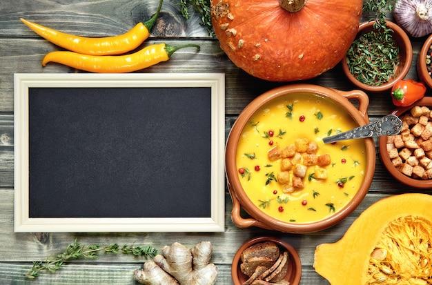 Пустая доска рядом с миской тыквенного супа и ингредиентов