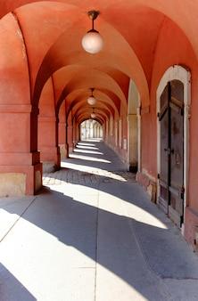 Узкий арочный проход, окрашенный в темно-красный цвет в старой праге