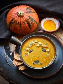Тыквенный крем-суп в керамической миске с тыквенными семечками, тимьяном и гренками на темном фоне