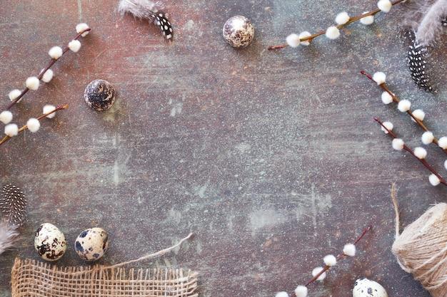 自然の春の装飾:ウズラの卵と羽、ネコヤナギの花、コピースペース