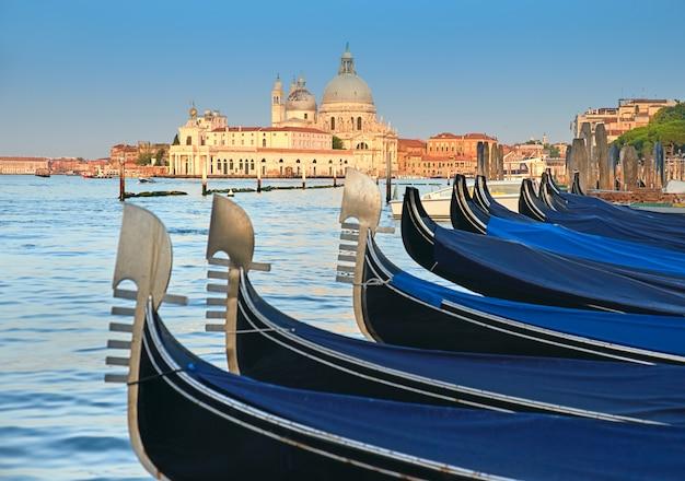 Гондолы на большом канале с базиликой санта мария делла салют в венеции