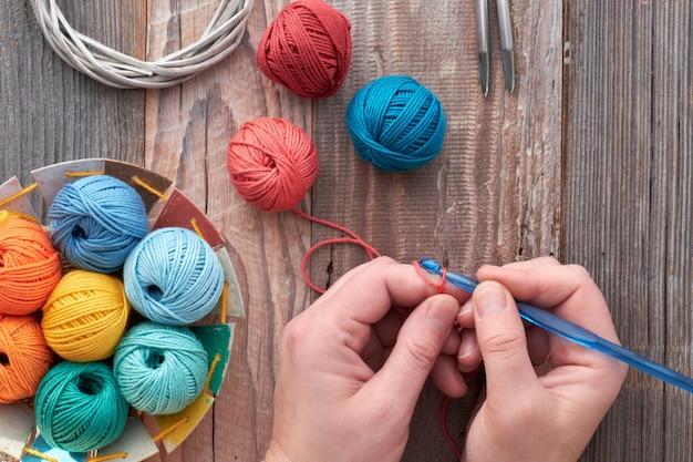 かぎ針編み、かぎ針編みのフックと糸のボールを持つ手に平面図、素朴な木の平面図