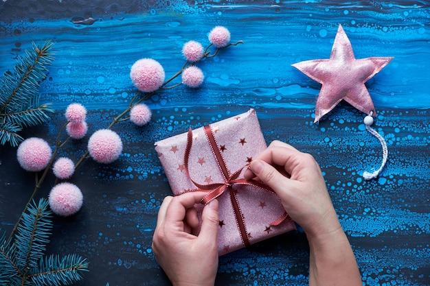 クリスマスプレゼント、冬の装飾、モミの小枝を包む女性の手。クリスマスフラットは、濃いアクリルの液体塗料の上に青、黒、ピンクで置きました。