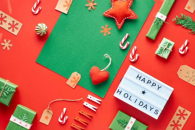 赤と緑のクリスマス。環境に優しいゼロ廃棄物のクリスマスと新年の装飾。ギフト、ボックス、コーヒーマグ、おもちゃで幾何学的なフラットレイアウト。テキスト付きのライトボックス