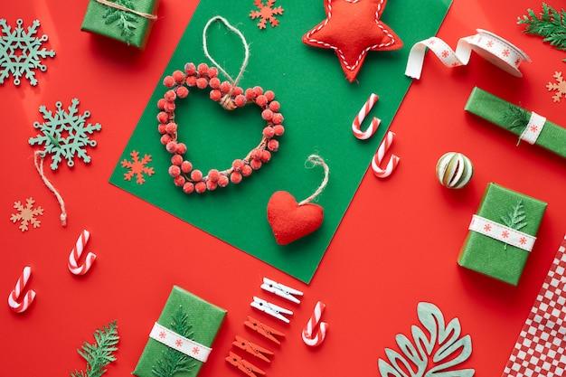赤と緑のクリスマス。トレンディな環境に優しいゼロ廃棄物のクリスマスと新年の装飾とギフト。幾何学的なフラットには、ギフト、装飾ボックス、ペグ、縞模様のキャンディー杖があります。