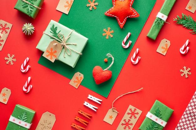 赤と緑のクリスマス。トレンディな環境に優しいゼロ廃棄物のクリスマスと新年の装飾とギフト。幾何学的なフラットには、ギフト、装飾ボックス、ペグ、雪片、縞模様のキャンディー杖があります。