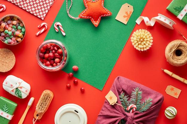 赤と緑のクリスマス。トレンディな環境に優しいゼロ廃棄物のクリスマスと新年の装飾とギフト。ギフト、装飾ボックス、竹製コーヒーマグ、キャンディーケーンを備えた幾何学的なフラット。
