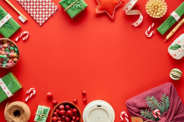 赤、緑、白のクリスマス。トレンディな環境に優しいゼロ廃棄物のクリスマスと新年の装飾とギフト。幾何学的なフラットには、ギフト、装飾品、装飾ボックス、縞模様のキャンディー杖があります。