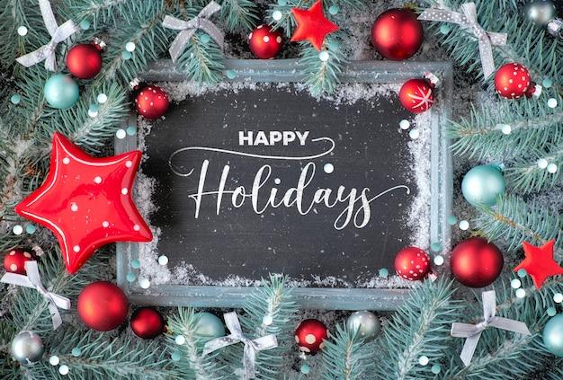 装飾されたチョークボードと緑と赤のクリスマス。雪で素朴な木のチョークボードの周りに装飾されたモミの小枝。テキスト付きフラットレイアウト