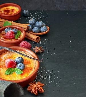 Крем-брюле с ягодами и ингредиентами на темном камне