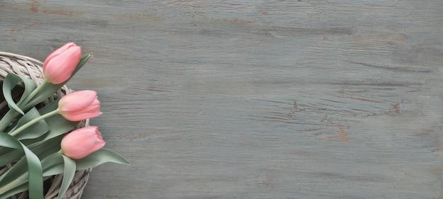 灰色の織り目加工の木製の編み輪のピンクのチューリップと春