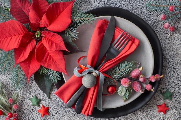 Рождественская сервировка на сером граните, тарелки, посуда, красная салфетка украшенная ягодами и пуансеттия