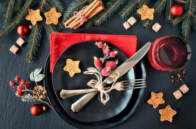 Черные тарелки и винтажные столовые приборы с елочными украшениями
