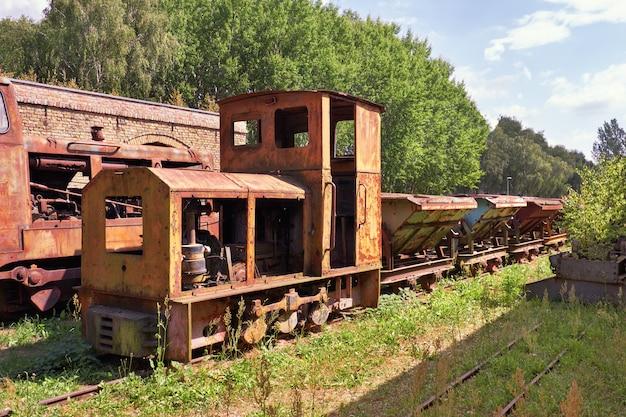 歴史的なレンガ工場の遺棄された錆びた蒸気機関車と石炭車