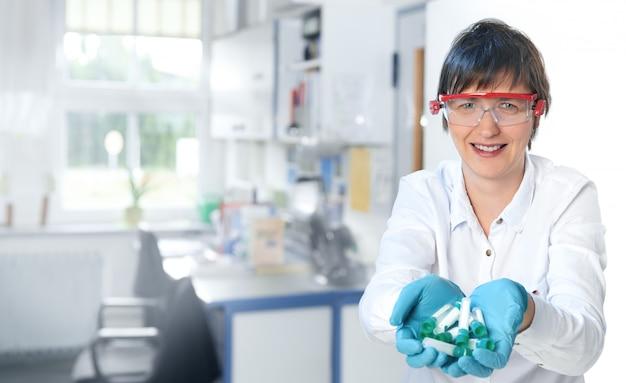 一握りのプラスチックチューブを持つ中年の女性科学者