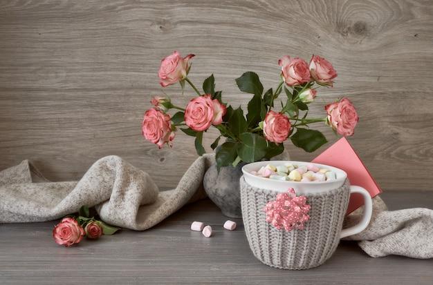バレンタインデーのマシュマロ、ピンクのバラ、グリーティングカードとホットチョコレートのカップのある静物