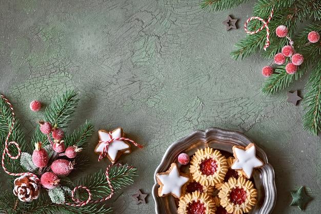 Плоская планировка с рождественскими украшениями зеленого и красного цвета с матовыми ягодами, безделушками и рождественским печеньем