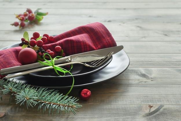 Концепция рождественского меню с черными тарелками и столовыми приборами, украшенными ветками елки, ягодами и лентами на дереве
