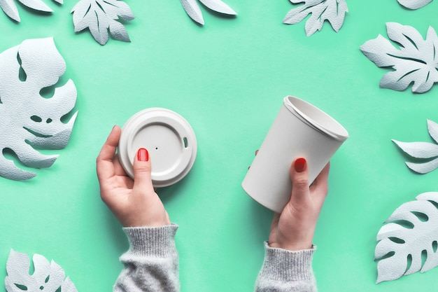 Стильная многоразовая эко кофейная кружка, бамбуковая чашка с крышкой в руках.