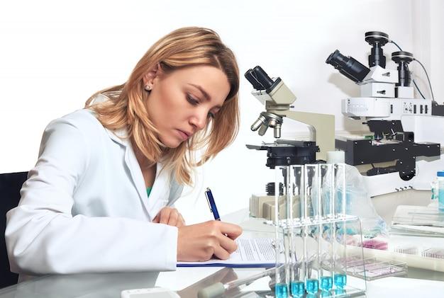 若い女性科学者または技術者が進捗報告書を書き留める