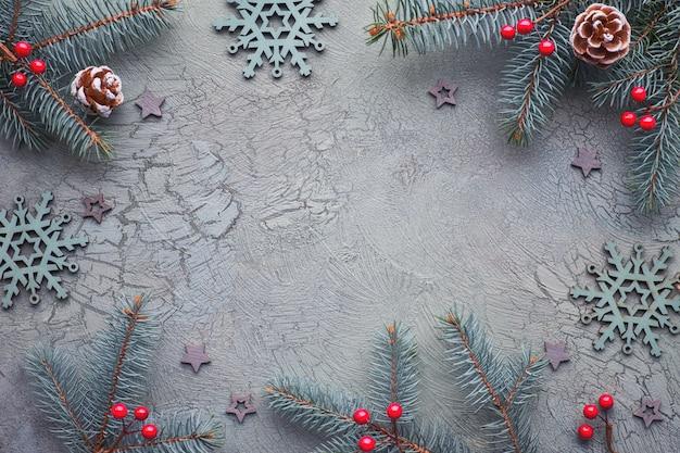 Плоская планировка с украшенными еловыми ветками на темной фактуре, зеленым и красным