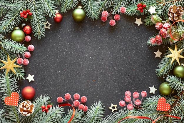 Новогодняя рамка с еловыми ветками, ягодами, безделушками и лентами красного и зеленого цвета,
