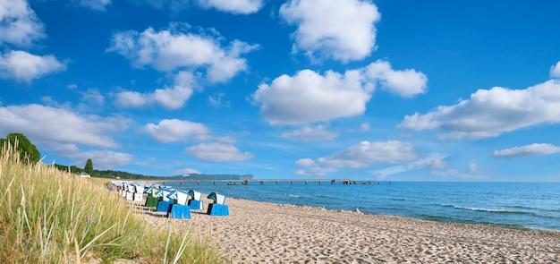 Песчаный пляж и традиционные деревянные шезлонги на острове рюген в германии