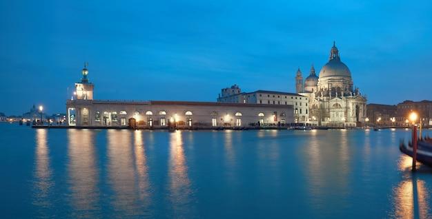 Освещенная пунта делла догана и церковь санта мария делла салюте в венеции, италия ночью