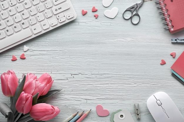 Весенняя плоская планировка с клавиатурой, мышью, розовыми тюльпанами, канцелярскими принадлежностями, открытками, декоративными сердечками и копией пространства