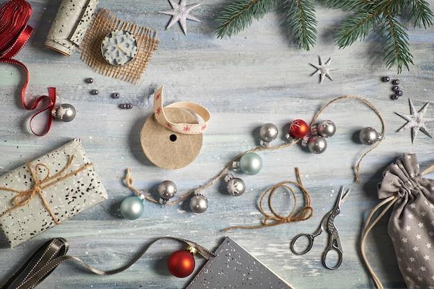 Деревенский деревянный фон в зеленый и красный с еловыми ветками, завернутые подарки и рождественские украшения