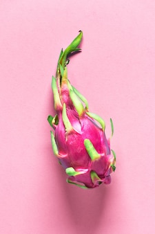 ピンクの紙の表面に新鮮な有機ピンク、白、緑のドラゴンフルーツと創造的なフラットレイアウト