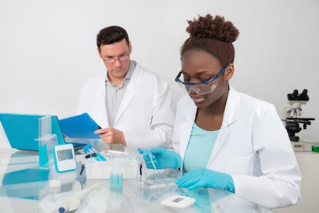 男性と女性の科学者が研究施設で働いています