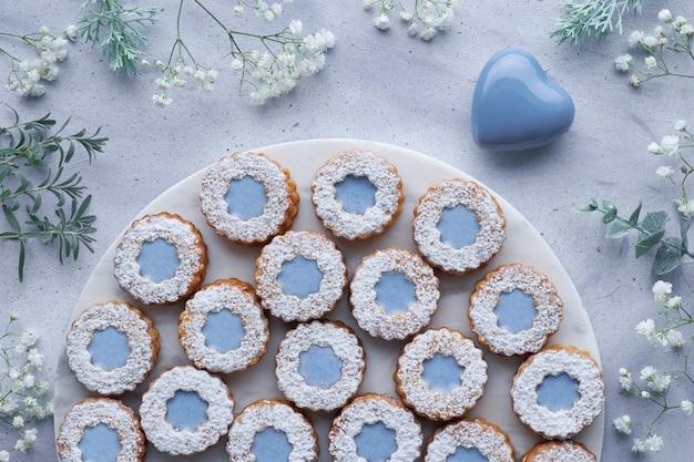白い花とセラミックハートで飾られた水色の青いガラスと花リンツァークッキーのトップビュー