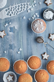 Вид сверху на стол с посыпанными сахаром маффинами, помадной глазурью и печеньем из рождественских звезд на синем дереве