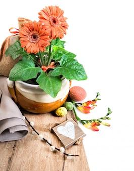 花と卵を白で隔離されるイースターアレンジメント