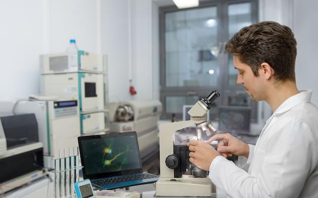 黒い髪と茶色の目を持つ科学者または技術者は、顕微鏡サンプルを使用します