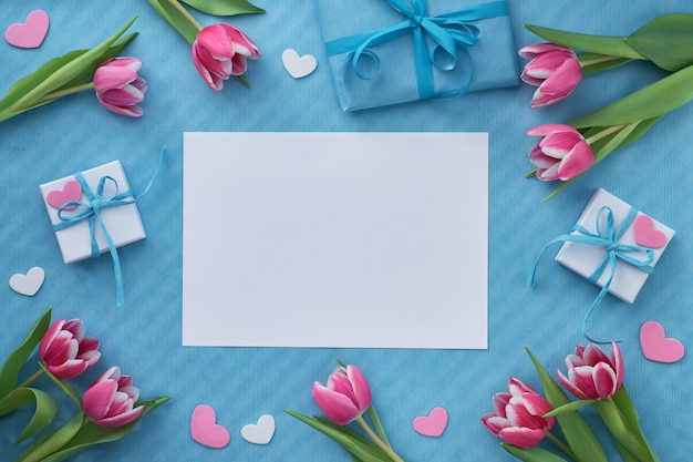 ギフト用の箱、ピンクのチューリップ、装飾的な心で春のフラットレイアウト、