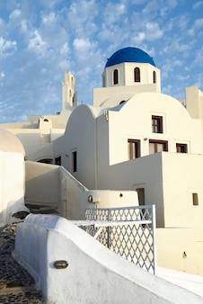 美しい白い家とサントリーニ島のイアの青いキューポラと地元の教会